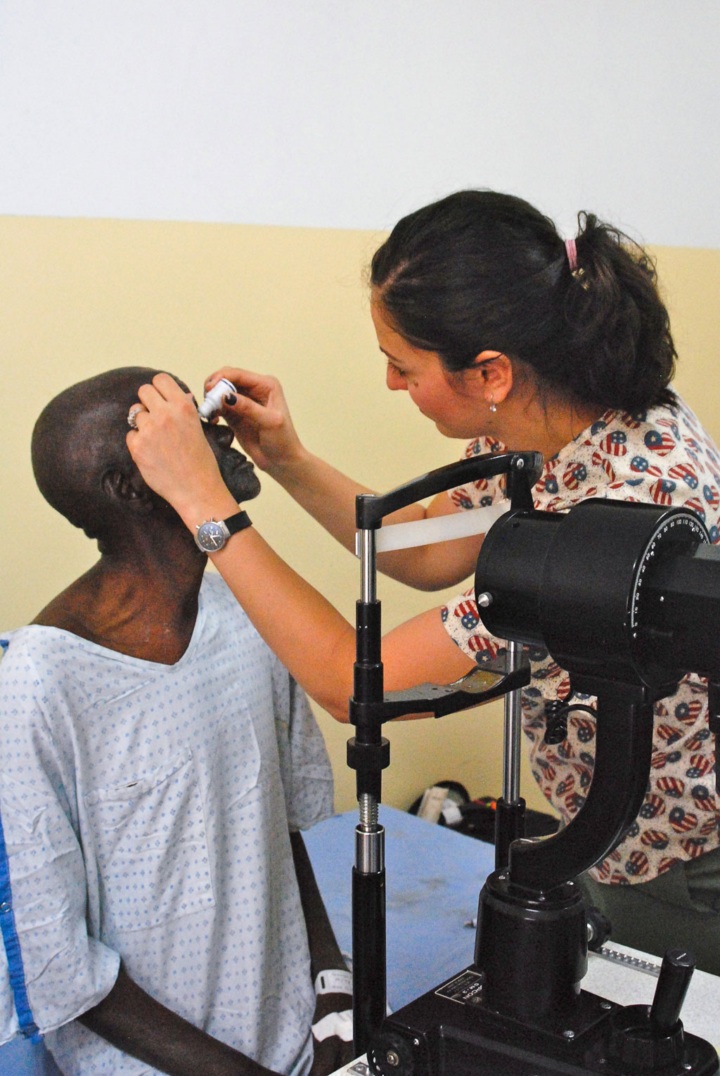 Zena applies dilating drops to a patient's eyes.