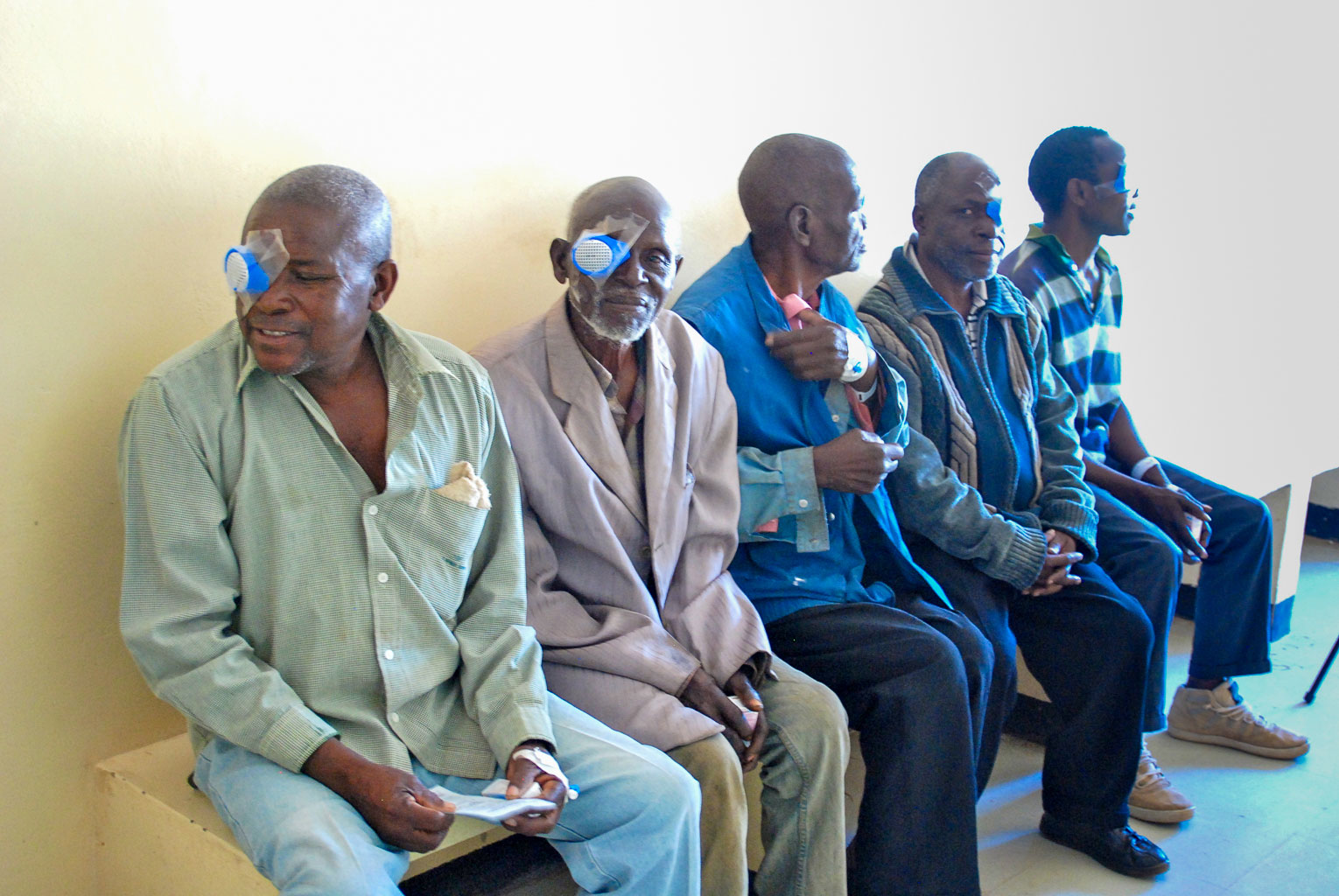 Post-surgery patients wait to have their eye bandages removed.